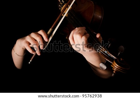 Female hands play a violin on black - stock photo