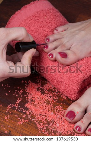 Female hands polish nail toes  in beauty salon - stock photo