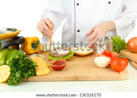 Female hands preparing cheeseburger, isolated on white