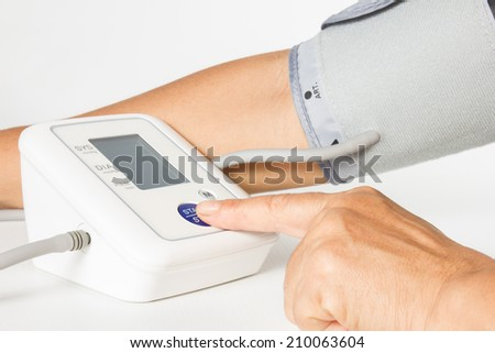 Female hands press start button on blood-pressure meter isolated on white background. - stock photo