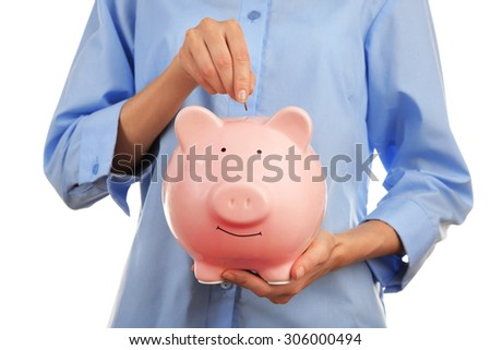 Female hands putting coin into pink piggy bank, closeup