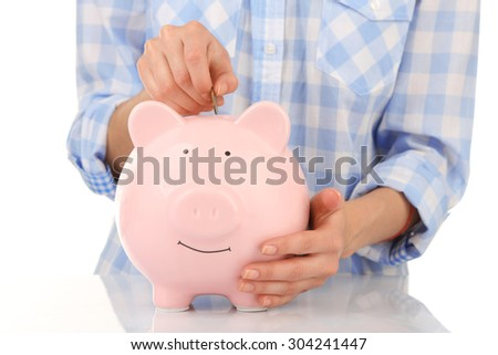 Female hands putting coin into pink piggy bank isolated on white