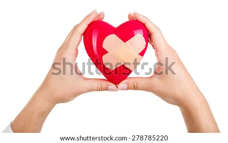 Female hands raised up holding red toy mended heart isolated on white background. Medical help or insurance concept. Cardiology care and health. Heart surgery and resuscitation concept - stock photo