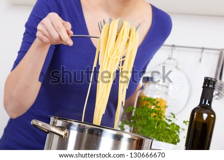 female hands raising cooked spaghettis out of the pot - stock photo