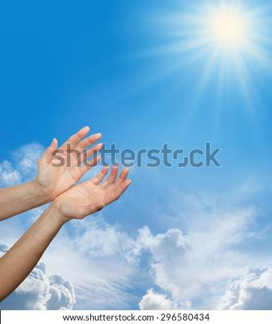 Female hands reaching up towards a bright sun burst on a blue sky background with fluffy clouds and plenty of copy space - stock photo