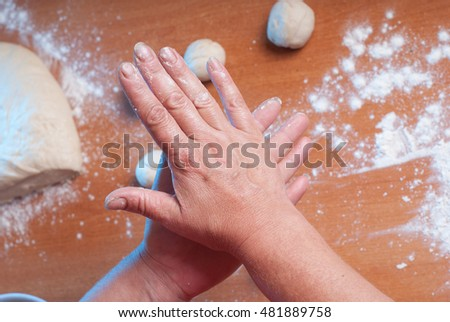 female hands rolling dough, the Baker prepares the dough, top view, first person
