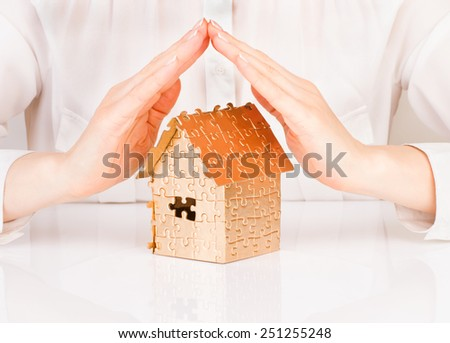 Female hands saving house of gold color - stock photo