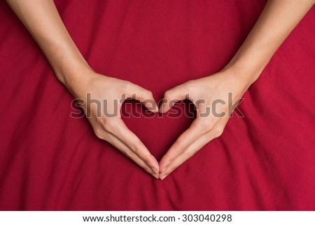 Female hands shaping a heart red background - stock photo