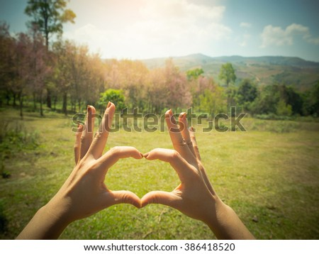 Female hands shaping a heart symbol on mountain background - stock photo
