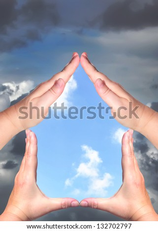 Female hands showing home sign with the storm sky outside and blue sunny sky inside - Family protect house concept