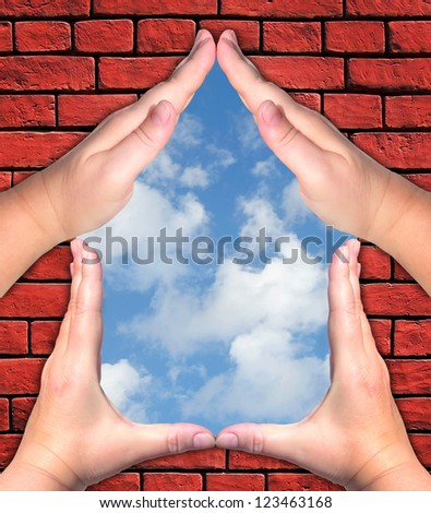 Female hands showing the home sign on the brick wall and blue sky background - Family future house concept - stock photo