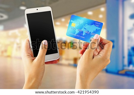 Female hands shows mobile smart phone and credit card, blurred background - stock photo