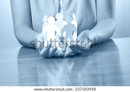 Female hands taking care of paper people, blueprint - stock photo