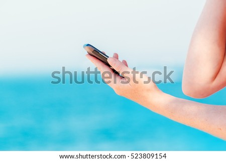 Female hands texting message on mobile phone on seaside, close up, selective focus