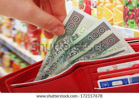 Female hands to get out the money from the purse on the shop background - stock photo