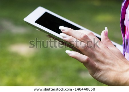 Female hands touching screen tablet PC in nature - stock photo