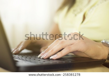 Female hands typing on a lap top - stock photo