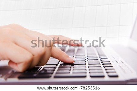 Female hands typing on a laptop at the office