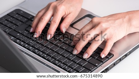 Female hands typing on a laptop keyboard