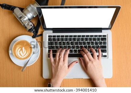 Female hands typing on a laptop keyboard with isolated screen and coffee relax time - stock photo