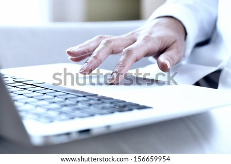 Female hands typing on a laptop track pad - stock photo