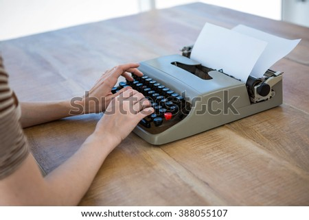 female hands typing on a typewrite that is on a wooden desk