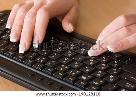 Female hands typing on keyboard.