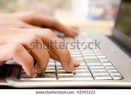 Female hands typing on Laptop Number Keys - stock photo