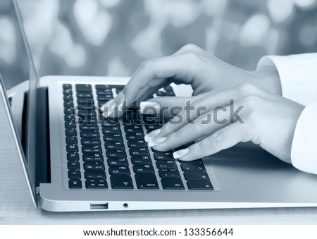 Female hands typing on laptot, close-up - stock photo