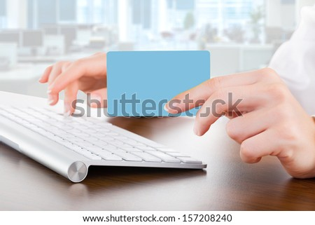 Female hands typing on white computer keyboard in office and give bank card - stock photo