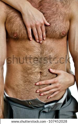 Female hands unbuckle mans pants. - stock photo