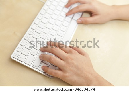 Female Hands Using Keyboard on Wooden Desk with Shallow Depth of Field