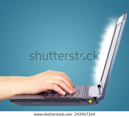 Female hands using laptop, side view, on light blue background