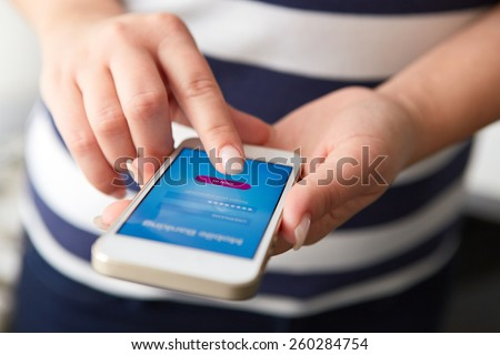 Female hands using mobile banking on white smartphone - stock photo