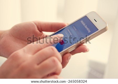 Female hands using mobile banking on white smartphone, toned - stock photo