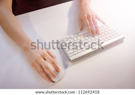 Female  hands using mouse and keyboard - stock photo