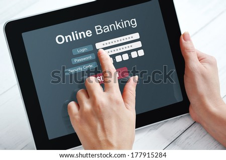 Female hands using online banking on touch screen device  - stock photo