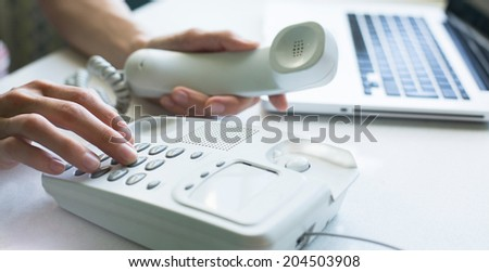 Female hands using phone, laptop at background