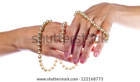 Female hands with a pearl necklace on a white background.