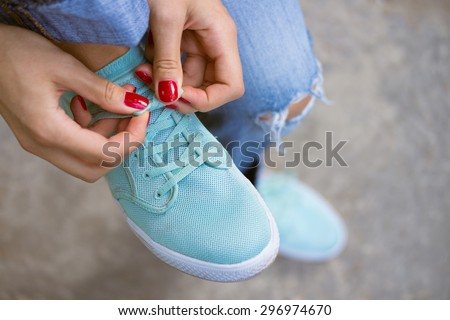 Female hands with a red manicure knotted laces on sports shoes. Young woman in blue jeans walking outdoors when she untied shoelace. A walk in the city. - stock photo