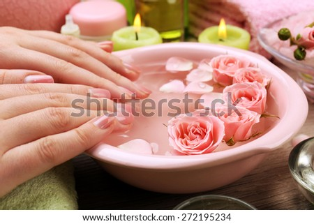 Female hands with bowl of aroma spa water on wooden table, closeup - stock photo
