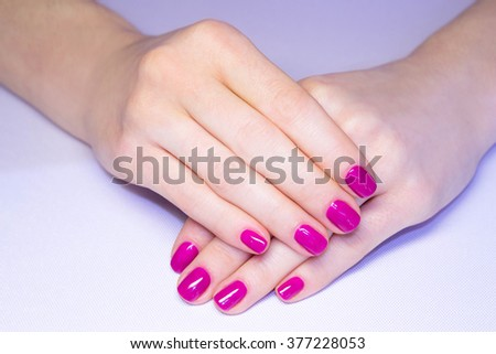 Female hands with bright polished pink nails on light background