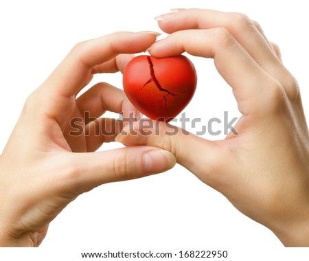 Female hands with broken red heart - stock photo