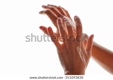 Female hands with cream isolated on white - stock photo