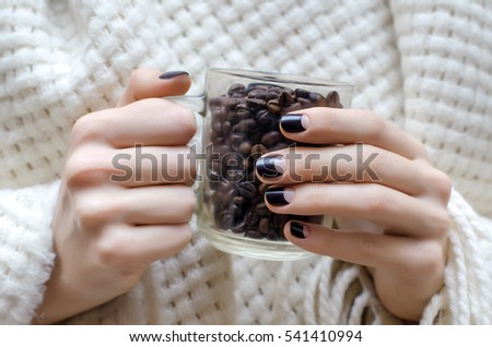 Female hands with dark brown nail design holding cup with coffee beans