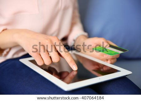 Female hands with digital tablet and credit card, closeup - stock photo
