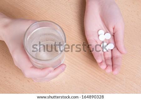 female hands with glass of water and tablets - stock photo