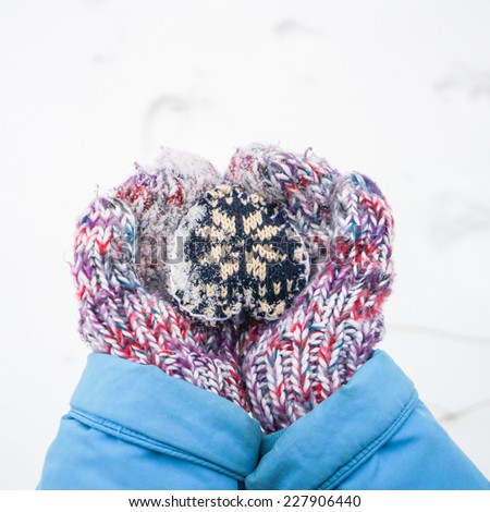 Female hands with hand made knitted heart over white snow background. focus on heart - stock photo