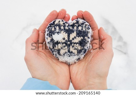 Female hands with hand made knitted heart over white snow background. Winter and Christmas concept