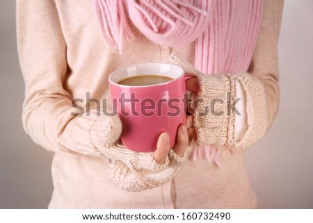 Female hands with hit drink, on light background